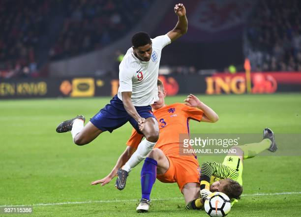 English player Marcus Rashford is stopped by Dutch player Matthijs de Ligt and Dutch goalkeeper Jeroen Zoet during a friendly football match between...