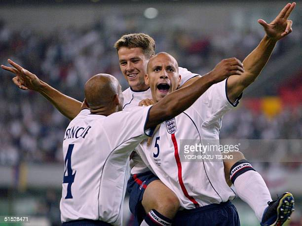 English players defender Trevor Sinclair and forward Michael Owen congratulate their teammate defender Rio Ferdinand after he scored his team's first...
