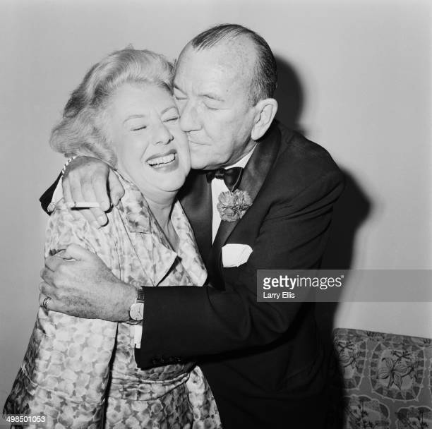 English playwright actor and director Noël Coward embraces actress Cicely Courtneidge the star of his new musical 'High Spirits' London UK 2nd...