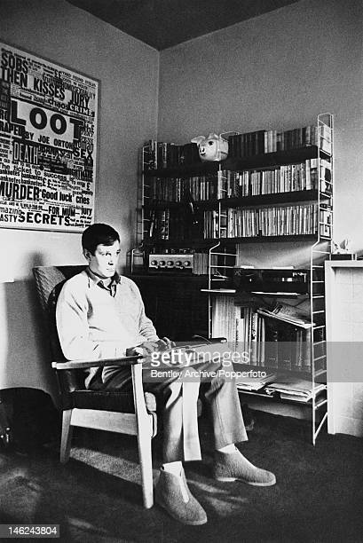 English playwright Joe Orton working at his flat in Noel Road Islington London circa 1966 Behind him is a poster for his play 'Loot'