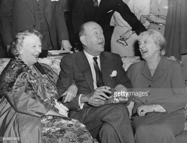 English playwright Noël Coward meets Marie Lohr and Dame Sybil Thorndike two members of the cast of his new play 'Waiting in the Wings' at the...