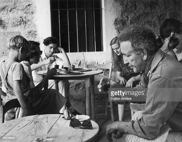 English poet, novelist, essayist and critic Robert Graves drinking at a cafe in Deya, Majorca, January 1954. On the left is his wife, Beryl and their...