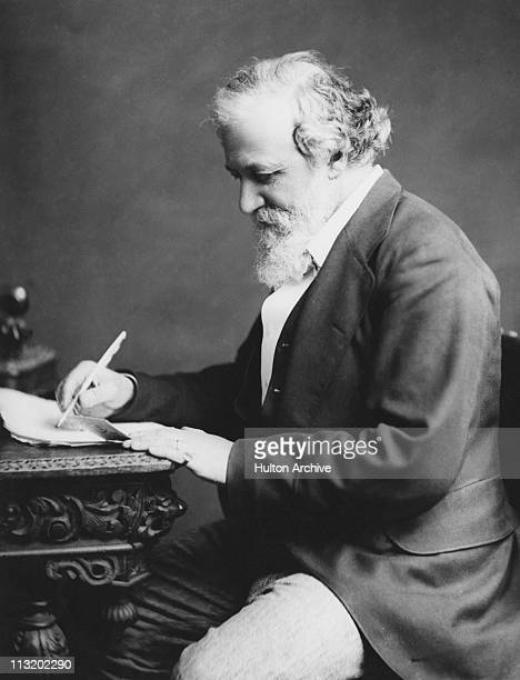English poet Robert Browning writng at a desk, circa 1880.