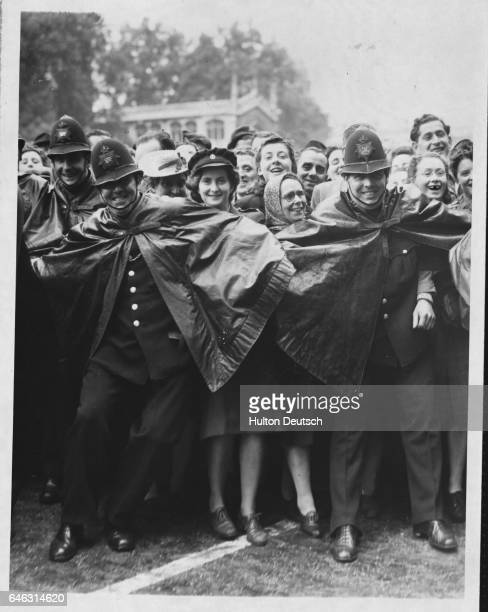 English policemen form a human barricade in order to contain a huge crowd at The House