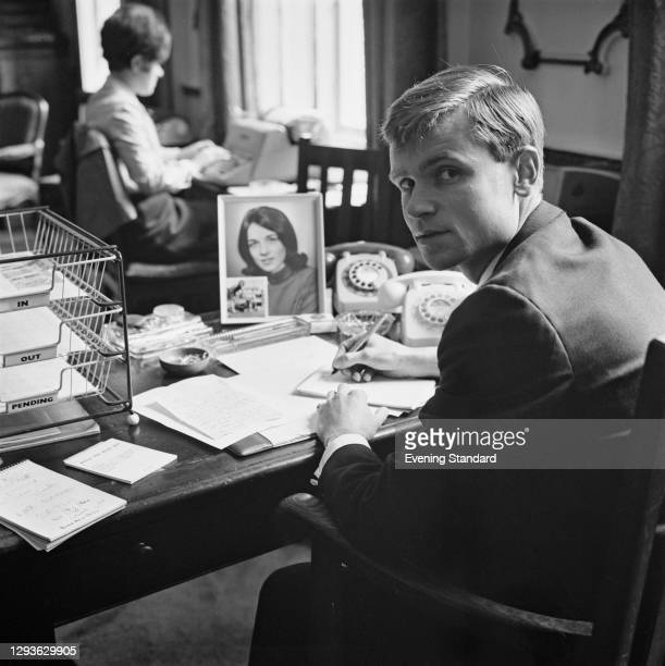 English politician and later novelist Jeffrey Archer, UK, 8th August 1966. On his desk is a photograph of his wife, scientist Mary Archer.