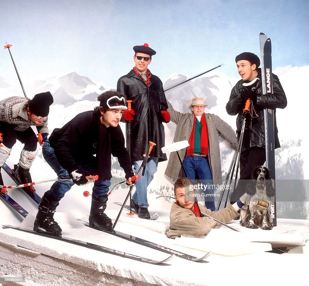 English pop and ska group Madness pose in a studio-bound alpine skiing scenario, circa 1985. Left to right: Lee Thompson, Chris Foreman, Suggs, Daniel Woodgate (bottom), Chas Smash and Mark Bedford.