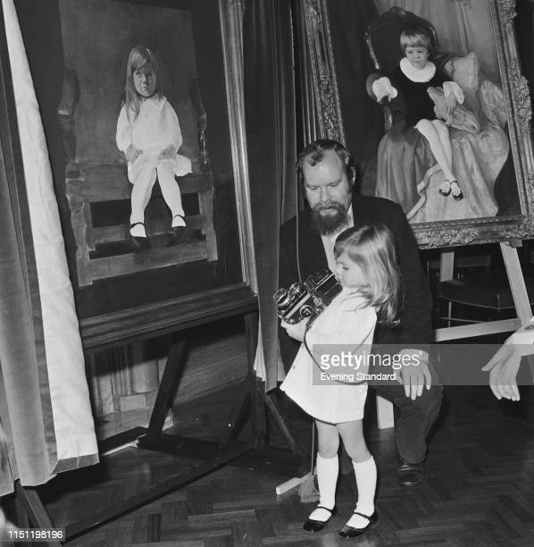 English pop artist Peter Blake with 3yearsold 'Miss Pears' Justine Hornby holding a medium format camera at the Painters Hall London UK 3rd December...