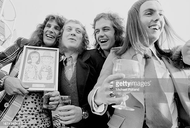 English pop group Slade with an award from Disc And Music Echo magazine London 14th February 1973 The award is a framed set of caricatures of the...