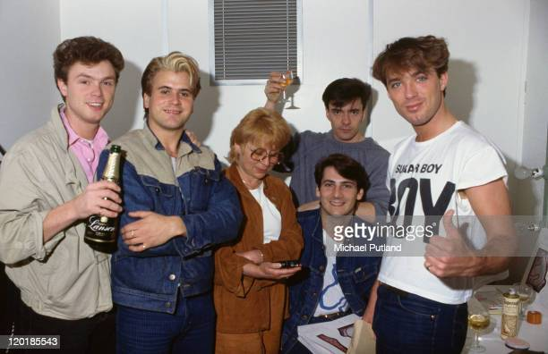 English pop group Spandau Ballet celebrating backstage, circa 1980. Left to right: guitarist Gary Kemp, saxophonist Steve Norman, unknown, drummer...