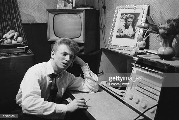 English pop idol Tommy Steele listens to his Ferguson Radiogram at his parents' home in Frean Street Bermondsey 25th February 1957 Original...