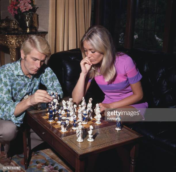 English pop singer Adam Faith playing chess at home with his wife Jackie Irving UK circa 1970