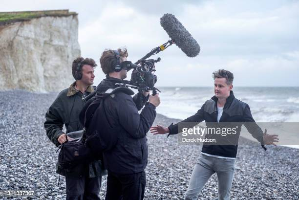English pop singer and musician Tom Chaplin pictured on the pebble beach at Birling Gap, near the resort town of Eastbourne being filmed to promote...