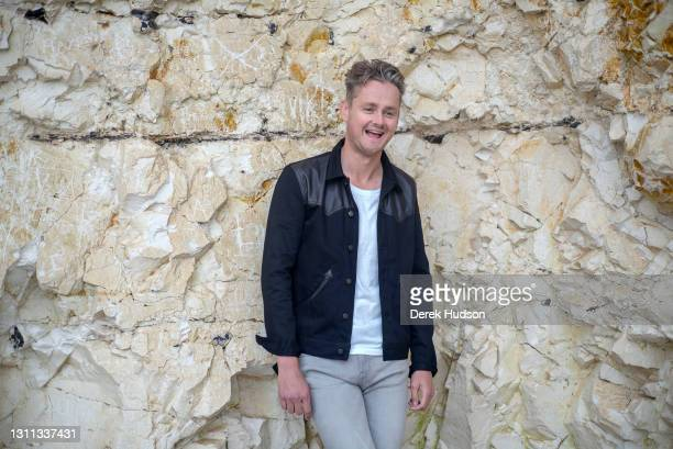 English pop singer and musician Tom Chaplin pictured on the pebble beach at Birling Gap, near the resort town of Eastbourne during a photo shoot to...