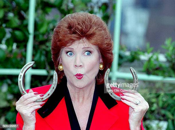 English pop singer and TV presenter Cilla Black holding a pair of lucky horseshoes on the roof of the Dorchester Hotel London 1985 Black was host of...
