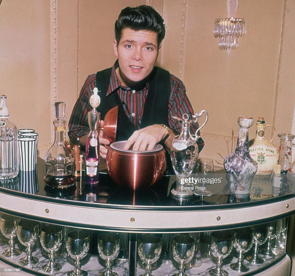 English pop singer Cliff Richard with his hand in an ice bucket at a cocktail bar, 1964.