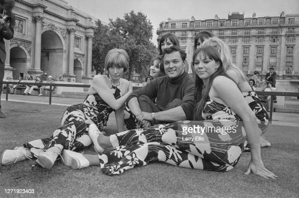 English pop singer Dickie Valentine posing at Marble Arch in London with the Beat Girls .