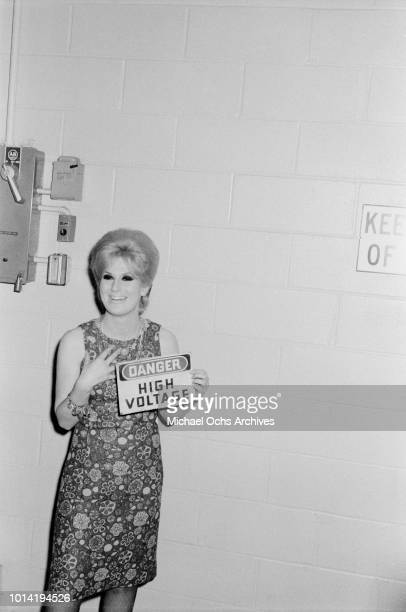 English pop singer Dusty Springfield holds up a sign reading 'Danger High Voltage' circa 1965