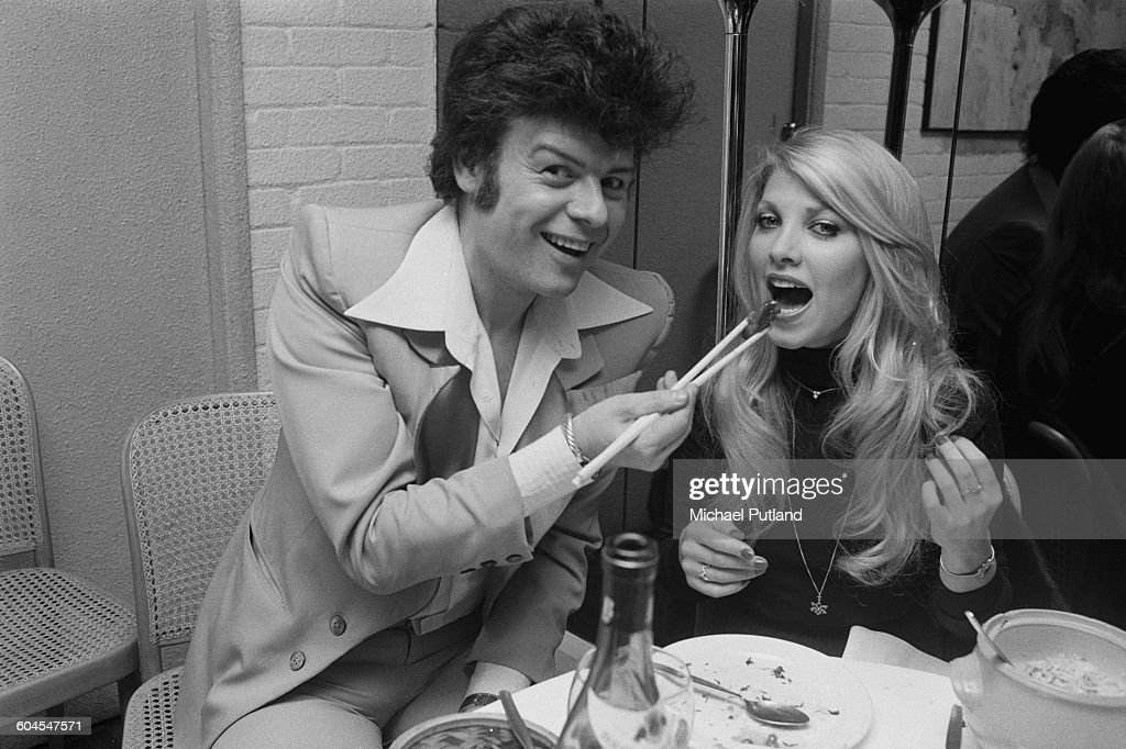English pop singer Gary Glitter using chopsticks to feed English singer-songwriter Lynsey de Paul (1948 - 2014) at a London restaurant, 14th March 1976.