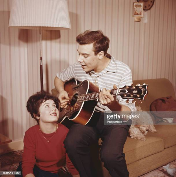 English pop singer Marty Wilde pictured playing a Gibson acoustic guitar with his wife Joyce in a living room at home in England in 1960