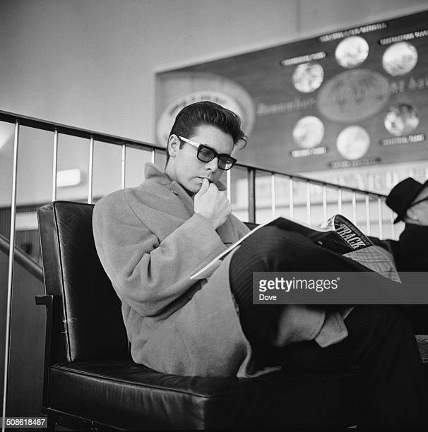 English pop singer musician performer and actor Cliff Richard reads a magazine whilst waiting at the airport 12th December 1964