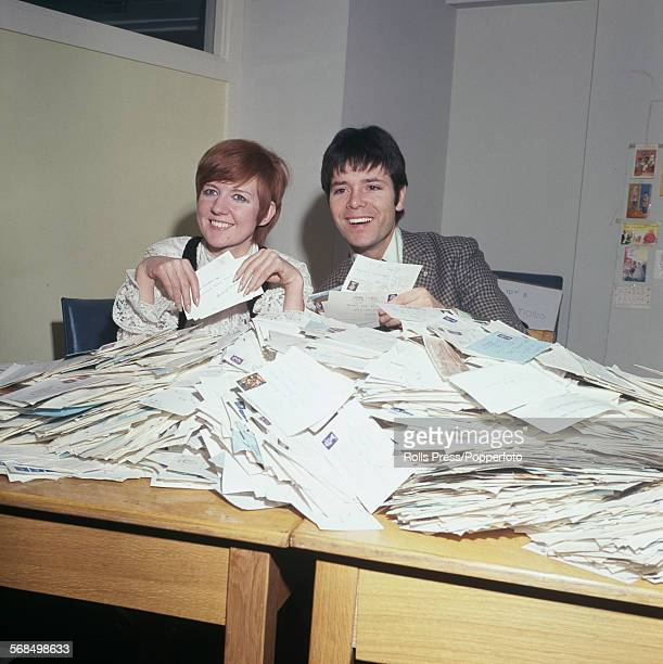 English pop singers Cilla Black and Cliff Richard helping to count the votes from BBC television viewers for 'A Song For Europe' the British...
