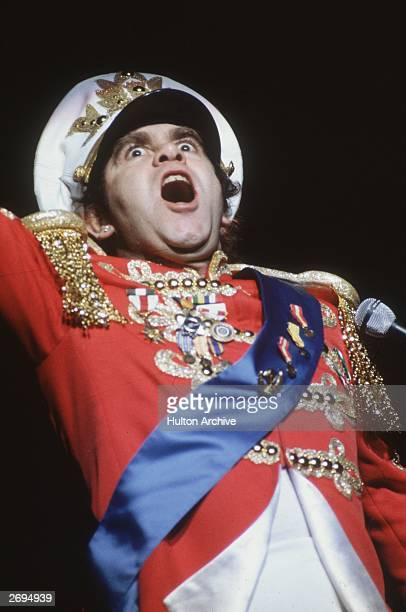 English pop star, Elton John, performing in a colourful costume at the Hammersmith Odeon.