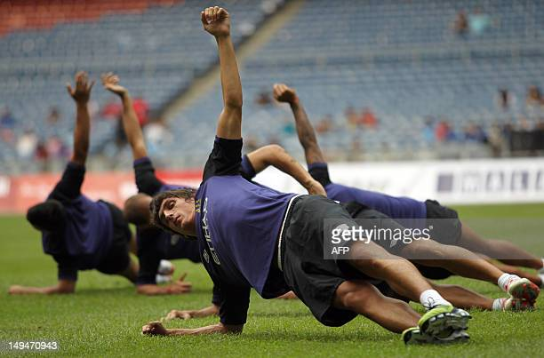 English Premier League champions Manchester City players warm up during a football training session at the Bukit Jalil stadium some 20 kilometres...