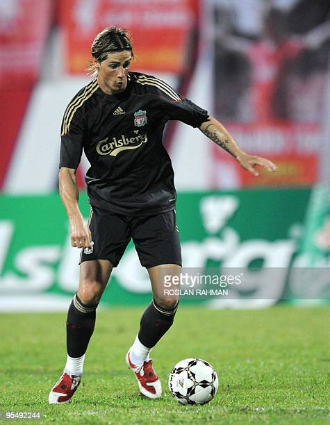 English Premier League club Liverpool's Spanish striker Fernando Torres prepares to pass the ball during a friendly football match against...
