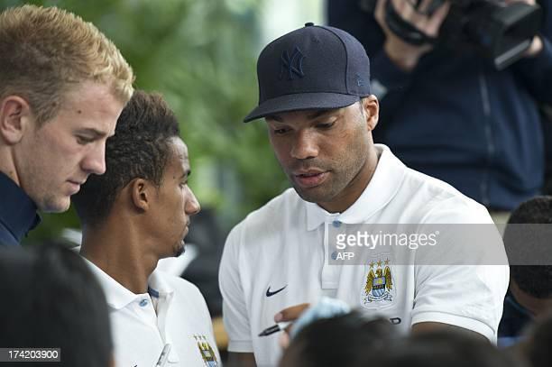 English Premier League football team Manchester City player Joleon Lescott signs autographs for fans as England goalkeeper Joe Hart and Scott...