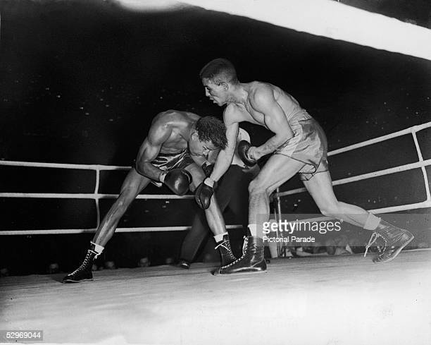 English professional boxer Randolph Turpin demonstrates his crouching style to American professional boxer Sugar Ray Robinson during the World...