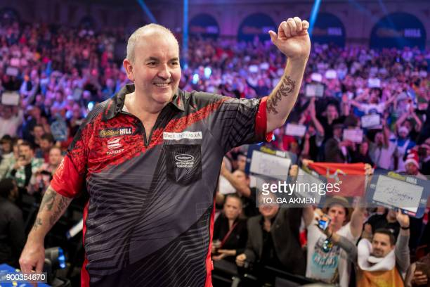 English professional darts player, Phil Taylor gestures to his supporters after losing to English professional darts player, Rob Cross at the PDC...