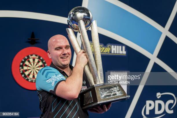 English professional darts player Rob Cross holds aloft the winner's trophy after beating English professional darts player Phil Taylor during the...