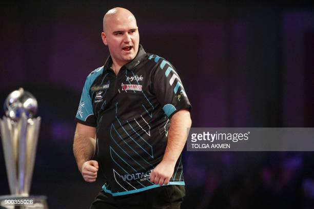 English professional darts player Rob Cross reacts as he competes against English professional darts player Phil Taylor at the PDC World Darts...