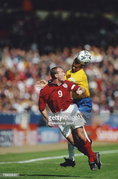 English professional footballer and captain of England Alan Shearer clashes with Brazilian defender Cafu during the International Friendly match...
