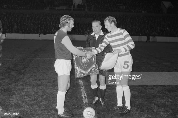 English professional footballer and captain of West Ham, Bobby Moore pictured on left exchanging pennants with Scottish footballer and captain of...