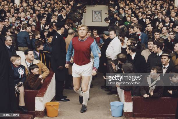 English professional footballer and defender with West Ham United Football Club Bobby Moore pictured leading the West Ham team out on the pitch at...