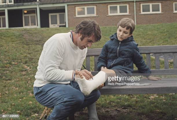 English professional footballer and forward with West Ham United Football Club Geoff Hurst signs the plaster cast on the leg of a young boy fan after...