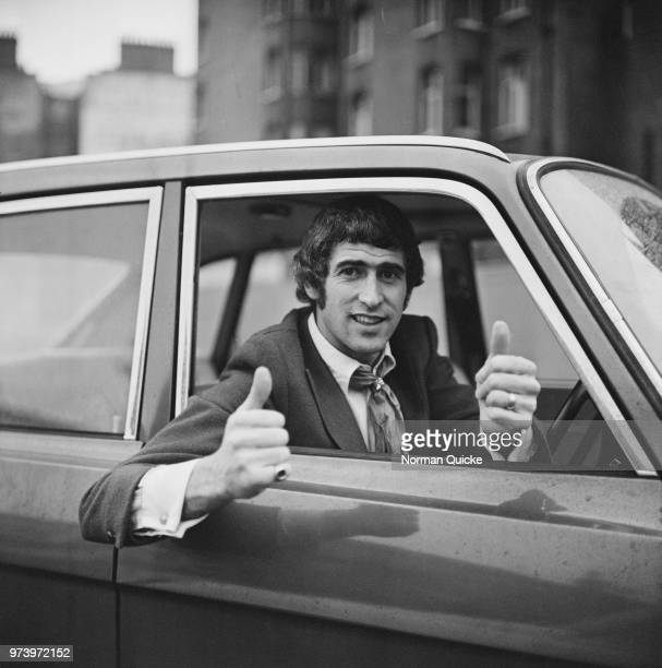 English professional footballer and goalkeeper for Chelsea FC Peter Bonetti pictured giving a 'thumbsup' sign from the driver's seat of his car in...