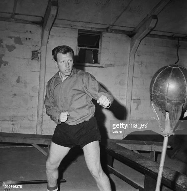 English professional footballer and goalkeeper with Bristol City FC, Mike Gibson pictured using a punching ball during a training exercise in a gym...