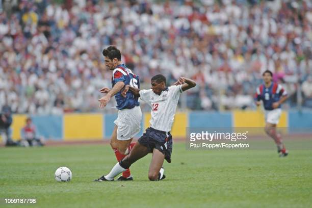 English professional footballer Carlton Palmer midfielder with Sheffield Wednesday moves in for a sliding tackle to stop advancing French player Eric...