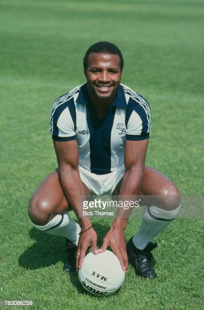 English professional footballer Cyrille Regis of West Bromwich Albion posed with a football on the pitch circa 1980