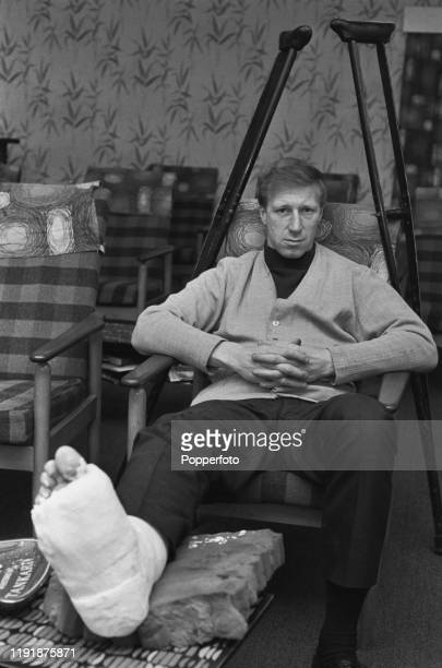 English professional footballer Jack Charlton defender with Leeds United seated on a chair resting his plastered foot on a table in June 1967 A pair...