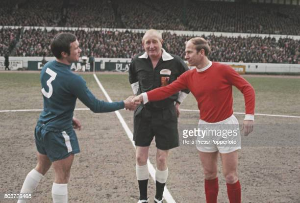 English professional footballers Bobby Charlton of Manchester United and Ron Harris of Chelsea shake hands in front of the referee at the centre spot...