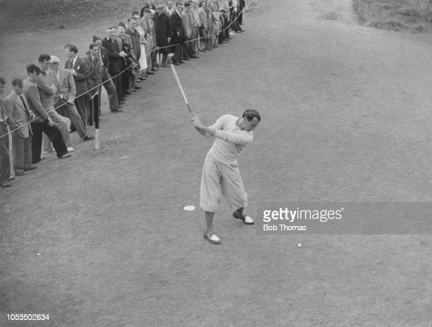 English professional golfer Max Faulkner tees off at the 13th during play to win the 1951 Open Championship at Royal Portrush Golf Club in County...