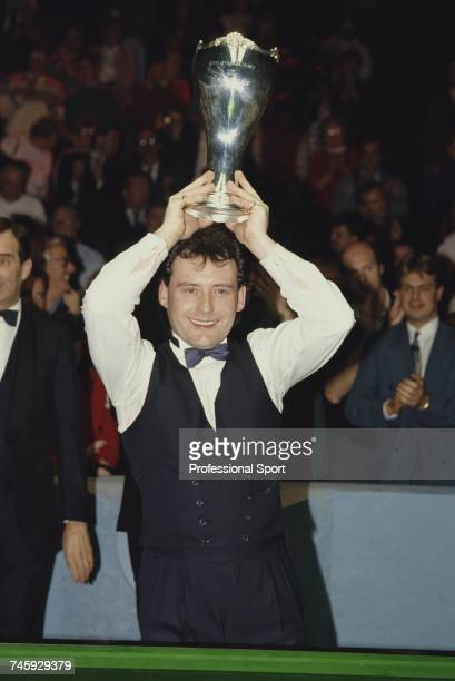 English professional snooker player Jimmy White holds the trophy above his head in celebration after beating John Parrott 16 frames to 9 in the final...