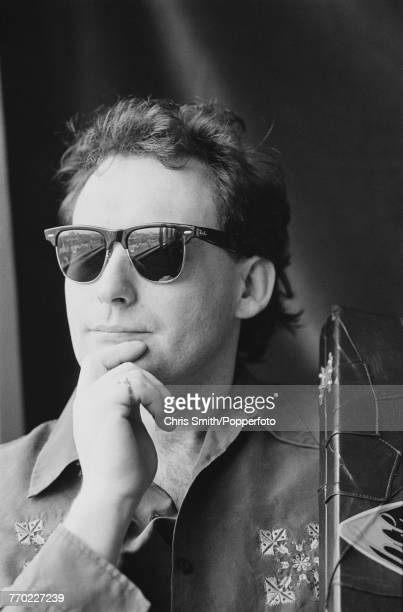 English professional snooker player Jimmy White posed wearing sunglasses holding his snooker cue case in England circa 1991