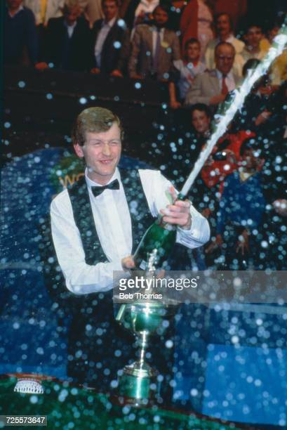 English professional snooker player Steve Davis celebrates with a large bottle of champagne sparkling wine after beating Joe Johnson 18 14 in the...