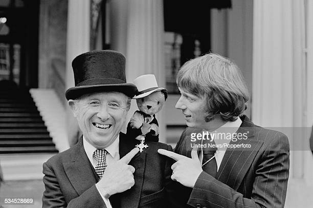 English puppeteer and entertainer Harry Corbett pictured with his OBE award puppet character Sooty and his son Matthew Corbett at an investiture...