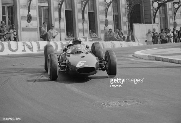 English racing driver Graham Hill drives the Owen Racing Organisation BRM P57 BRM P56 1.5 V8 racing car during competition to finish in first place...