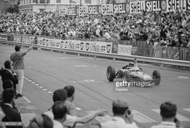 English racing driver Graham Hill drives the Owen Racing Organisation BRM P57 BRM P56 1.5 V8 racing car over the finish line to win the 1963 Monaco...